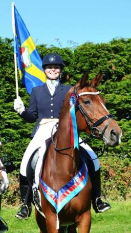 Charlie Hunt on Isaura Van't Ceusterhof holding the Pembrokeshire flag..jpg