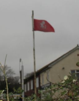 The flag of Kent caught in a breeze at the entrance to the Romney, Hythe and Dymchurch railway line in Hythe.