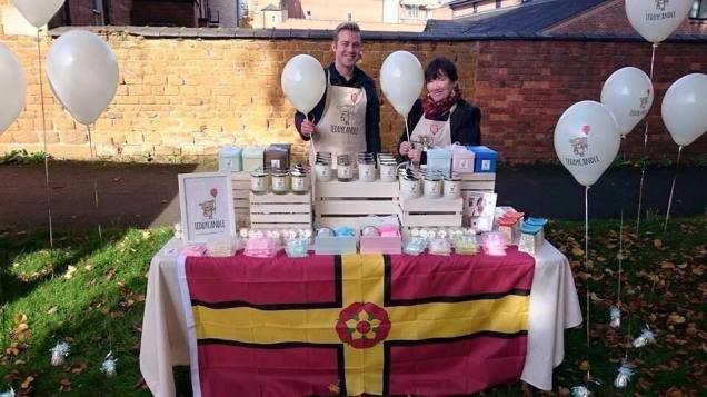 A stall in Northampton selling candles, on the recent Northamptonshire Day bedecked with the county flag