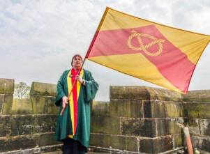 Carol Lake of the Stafford Burgesses Guild with the Staffordshire county flag on the roof of Caverswall Castle