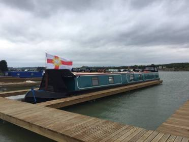 The West Riding flag unfurls in a breeze over a barge.